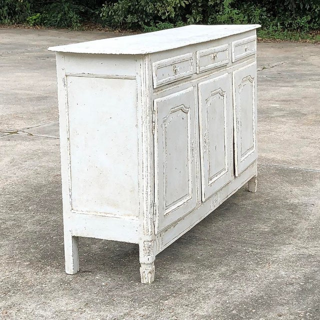 18th Century Country French Louis XVI Painted Buffet features a tailored look with only a touch of carved detail on the...