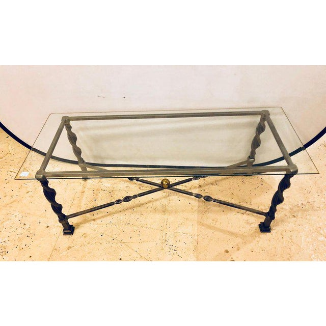 A Hollywood Regency style brass and steel glass top coffee table in the manner of Maison Jansen. This strong and heavy...