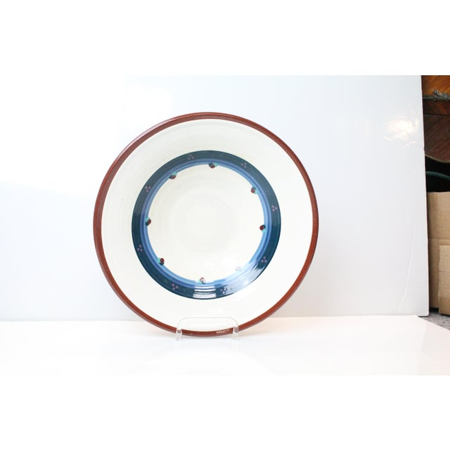 Lynn Duryea signed pottery shallow bowl in white with blue and purple motifs with red edge. From Portland, Maine.
