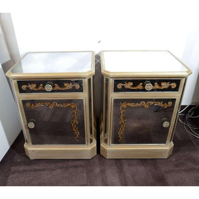 Pair of antique mirrored end tables with gilt wood frames and reverse hand painted eglomise designs. Each is fitted with a...