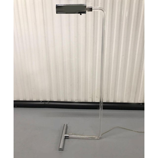 Striking Lucite and chrome modernist floor lamp, circa 1970s. T-shaped foot and conical lamp head. Chrome is highly...