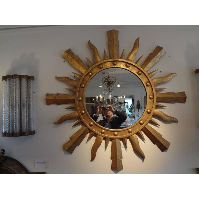 Large Italian gilt iron Gilbert Poillerat style sunburst mirror. Measures: 47.25 in diameter.