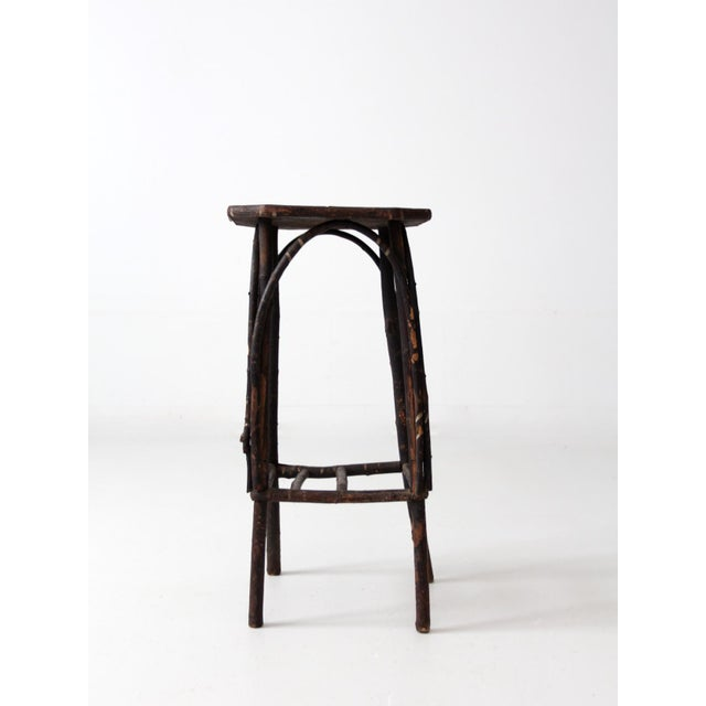 This is an antique Adirondack twig table. The slender end table features a bentwood twig frame with open slat shelf and...
