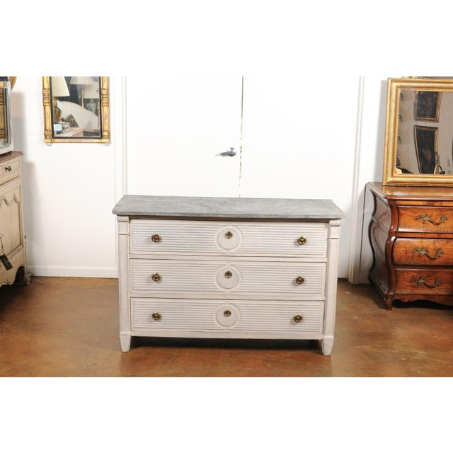 A Belgian Gustavian style painted wood three-drawer commode from the mid-19th century, with faux-marble top and reeded...