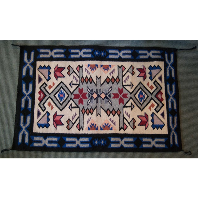 Enrich your living space with this tasteful vintage Navajo rug. The piece is beautifully executed from wool fabric and...