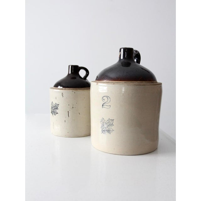 Beautifully aged, these are striking antique Western Stoneware utilitarian jugs. The set includes a 2 gallon and 1 gallon...