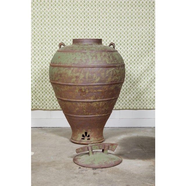 Large urn shaped clay jar with ornamental lid having a bronze and green patina and stamped by the maker. The jar has a...