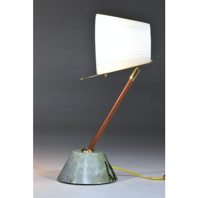 Contemporary handcrafted articulating table lamp designed in a gold polished brass stem adorned with a brown sheathed...