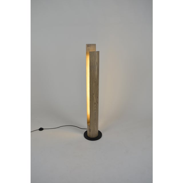 Wooden columnar floor lamp made from a single over-sized ash dowel and having a brass accent plate located at the bottom...