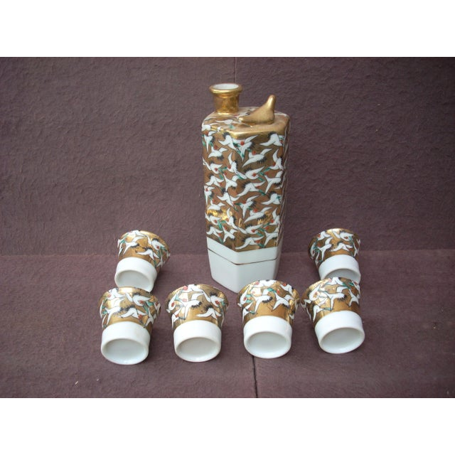 """Hexagonal special ceramic bottle marked """"Genuine Kutani"""" in English with six flared saki cups; bright gold background with..."""