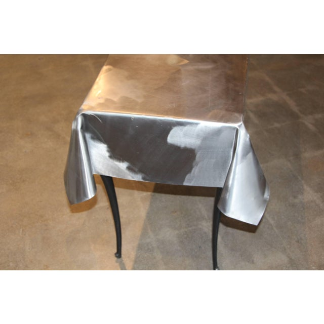 A most unusual metal draped console table with legs. A magnet sticks to the top so it may be some sort of steel. The...