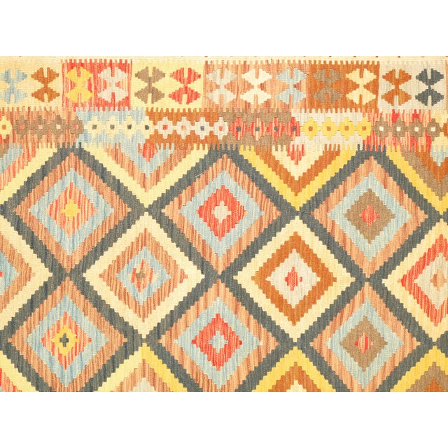 Yellow vintage Anatolian flat-weave kilim rug is masterfully hand-knotted of top quality wool for enduring beauty. A...