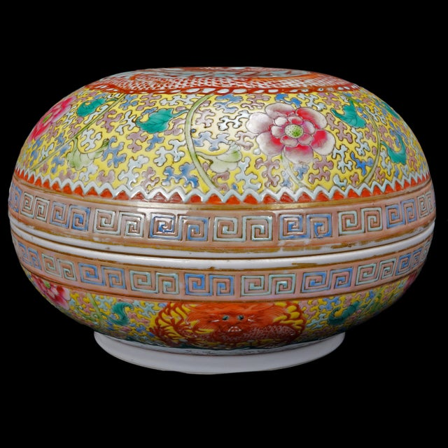 A round over glaze enameled porcelain box with an imperial five-clawed dragon with blossoming peony flower motif that...