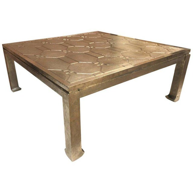 Silver clad coffee table style of James Mont. Table has a wooden base and is silver clad. Has a silver-etched top.