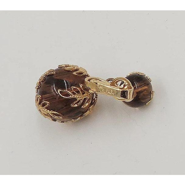"Early 1950s goldtone filigree striated semi-translucent Lucite faux-tortoise clip back earrings. Marked ""Trifari.""..."