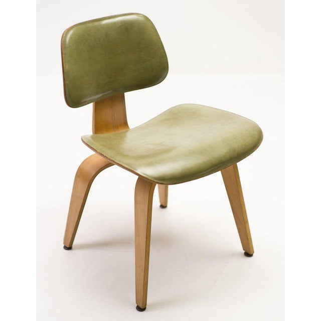 DCW designed by Charles & Ray Eames in ash with original leather seat and back. Original upholstery label with delivery...