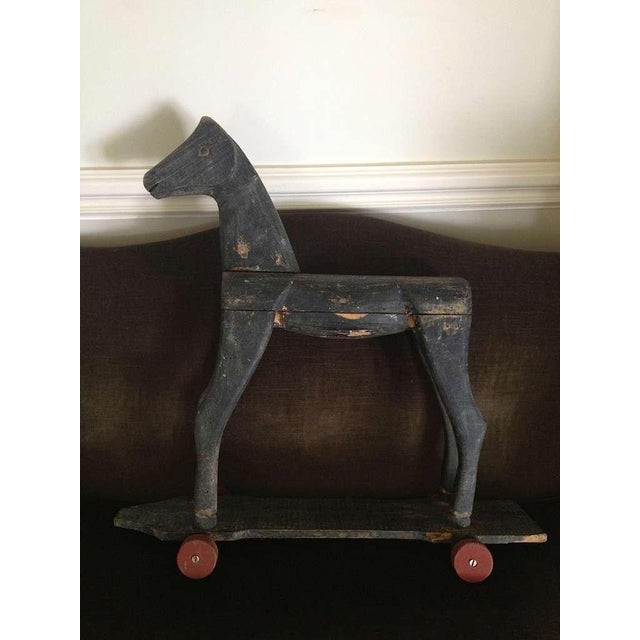 Black painted and carved wood on red wheels, brass eyes. Charming and rustic.