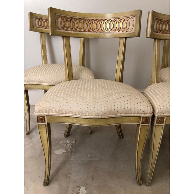 Sophisticated set of four Klismos chairs having sensuously curved legs and back. Gold gilt raised ring pattern is...