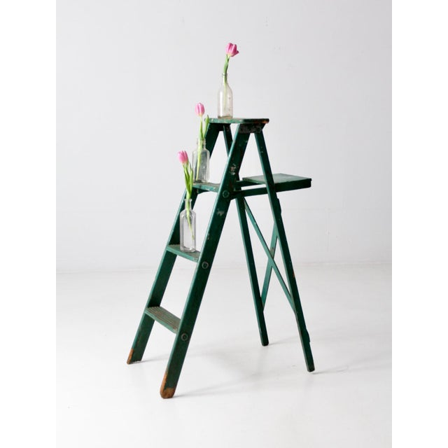 This is a vintage green wooden ladder. The painted a-frame ladder features three grooved steps, a back shelf, and crossing...