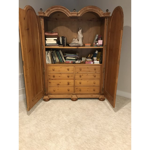 Double bonnet armoire with ebony columns and trim. Bun feet. Eight drawer storage with dividers. Large open area top shelf...