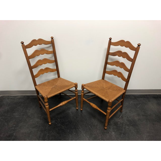 A pair of dining side chairs by Ethan Allen. Made in the USA in the late 20th Century. Farmhouse style with ladder backs,...