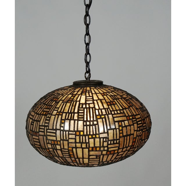 A gorgeous, multifaceted, flattened sphere pendant light by artist Adam Kurtzman, who is known for his sculpture, using a...