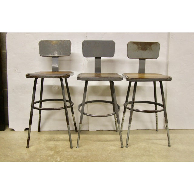 Set of 3 Royal Metal industrial stools, ca.1940s. Feature a square seat with an applied masonite top and adjustable legs....