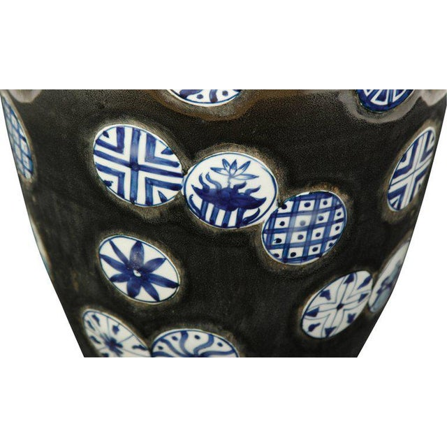An unusual pair of Chinese export porcelain vases, with blue and white circles of different patterns on a black matte...