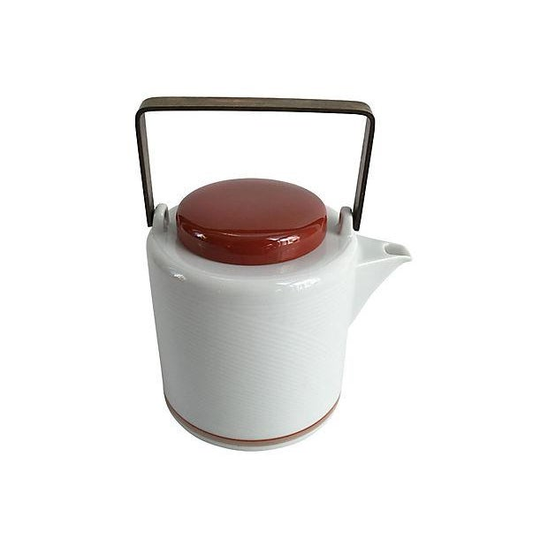 Jack Lenor Larsen for Dansk modernist white porcelain teapot with brass handles and cranberry-colored lid. Maker's mark on...