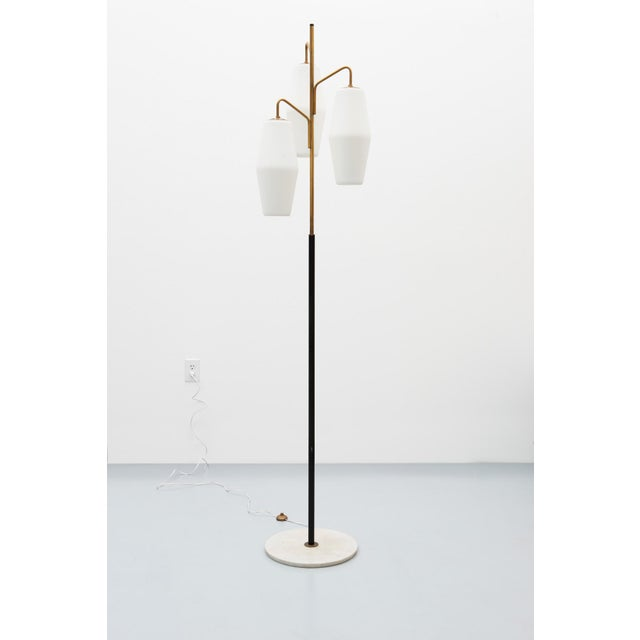 A handsome floor lamp in opaline glass, brass, Carrara marble and lacquered steel by Stilnovo. With original marking....