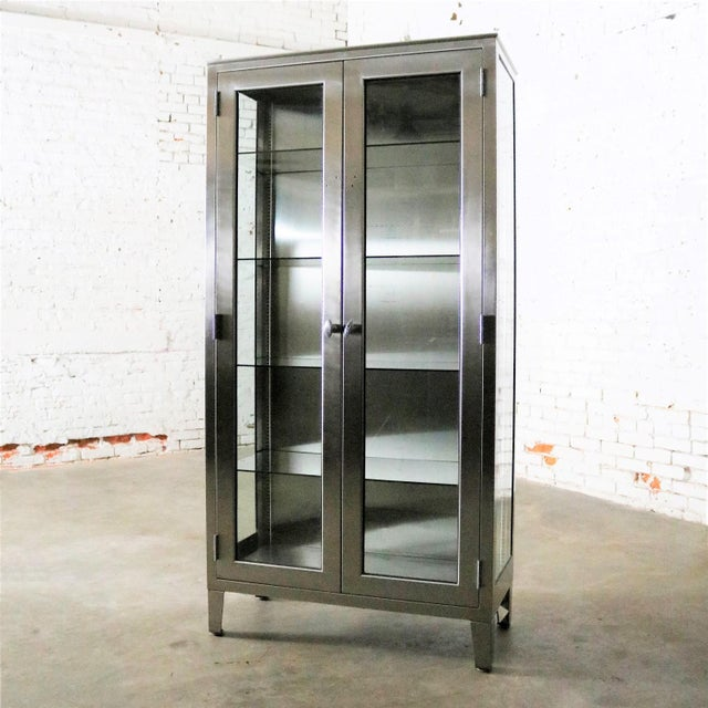 Incredible industrial stainless-steel medical or apothecary cabinet with glass doors, sides, and shelves that allow it to...