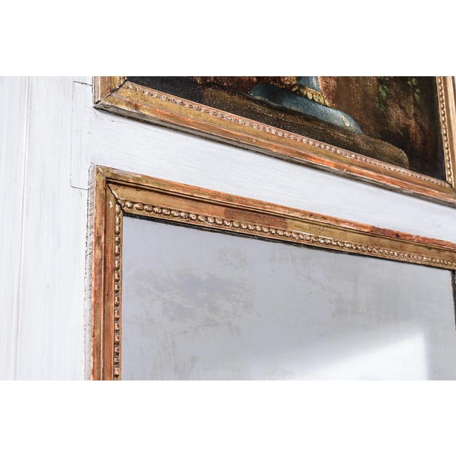 Antique trumeau mirror, with painting of flowers at top.
