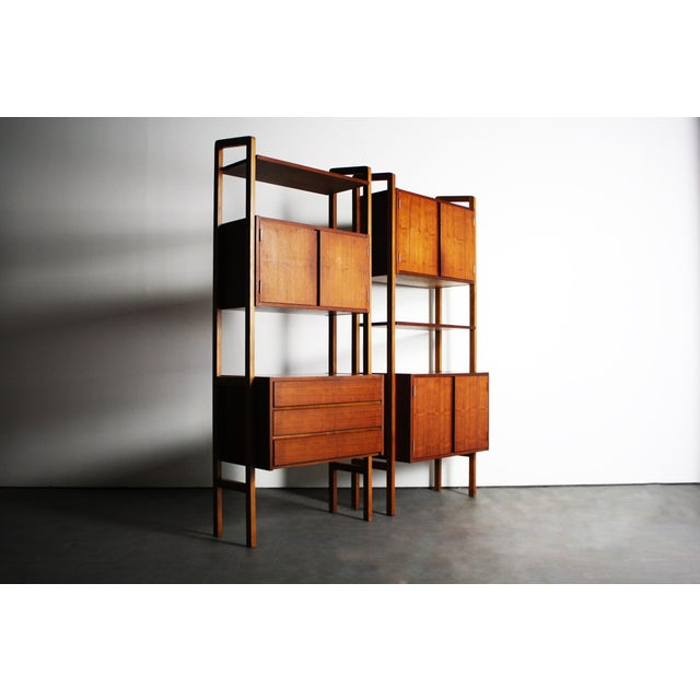 Pair of Mid-Century wall units. This extremely versatile teak wall unit allows so much for a room. Be it used for a bold...