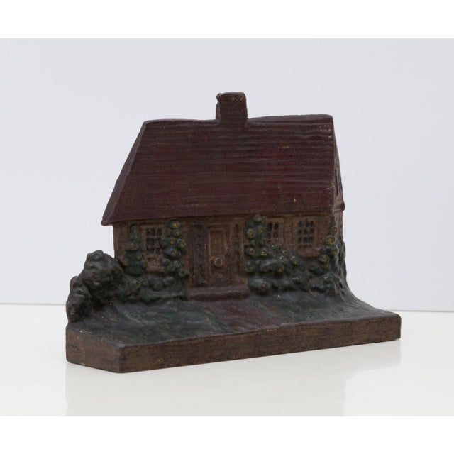 Very hefty solid cast iron door stop statue in the form of a charming country cottage with garden. Original red and green...