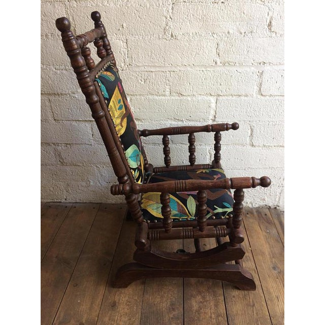 A fabulous recycled wood rocker for a small child covered in a playful swinging monkey textile with a flash of aqua silk...