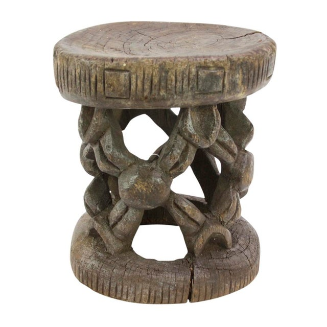 This tribal piece was hand carved to display a repeating web-like pattern, and markings on the side of the base and seat....