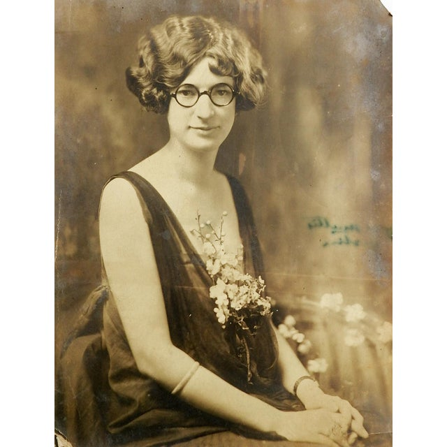 Circa 1920 vintage portrait of a young woman with round glasses, plunging neckline covered by flowers. Corner creases,...
