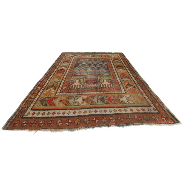 Offered is a beautiful Russian area rug. This rug is composed of hand knotted wool and features tones of rust, brown, and...