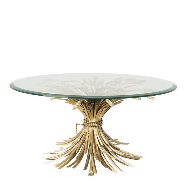The Glass Top Gold Coffee Table reflects uniqueness on its meticulous base design resembling wheat branches on antique...