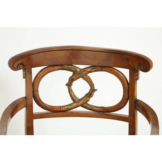 A pair of graceful and elegant fruitwood Biedermeier arm chairs with a double ring design on back with gilt wood accents....