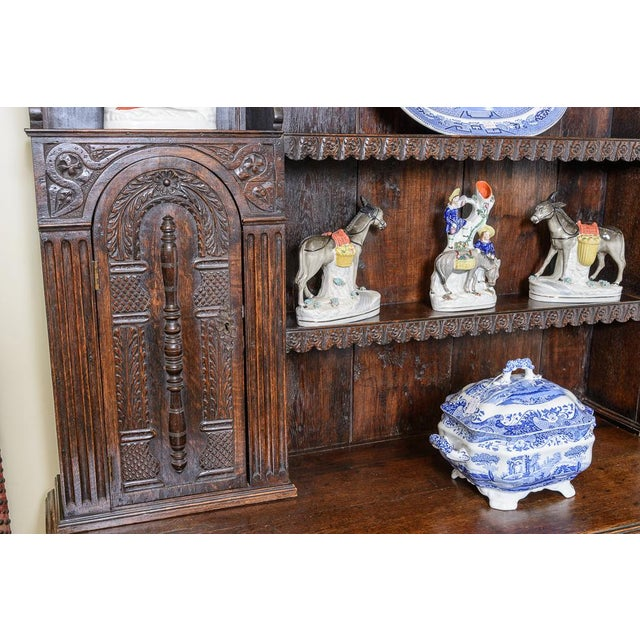 Most unusual antique English carved oak dresser with rack, shelves and cupboards on a three drawer base with cabriole legs.