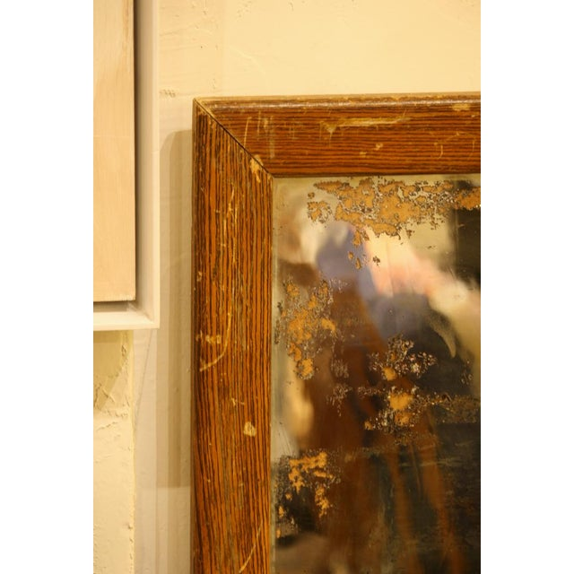 This is a vintage faux wood grain and metal mirror.