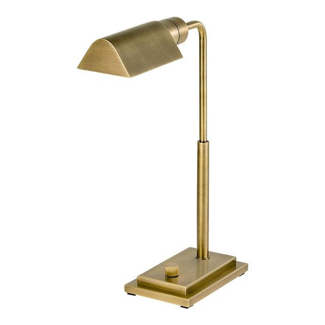 An English brass desk light with a rectangular stepped base, tubular column and traingular canopy. The light has a knurled...