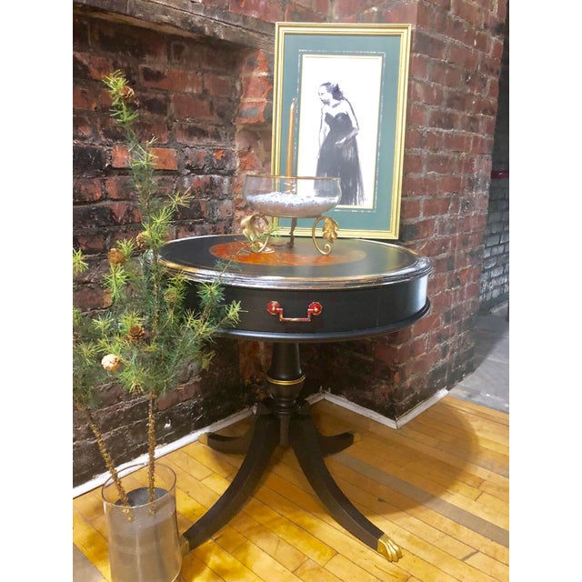 Vintage round leather top foyer table. Painted in ink black and partially distressed with yellow and white accent colors....