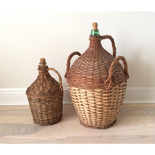 A pair of two vintage demijohn bottles with original woven wicker casings. The larger size has three handles and green...