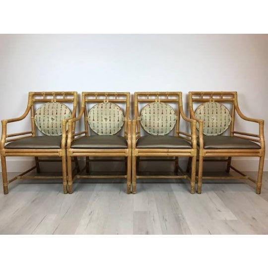 Set of 4 Vintage Rattan Arm Chair in the style of Ficks Reed or McGuire High quality Rattan with rawhide lacing, vinyl...