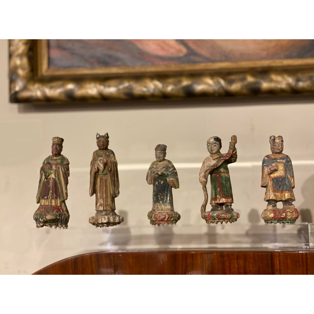 Five antique hand carved Chinese figures mounted on an acrylic base.