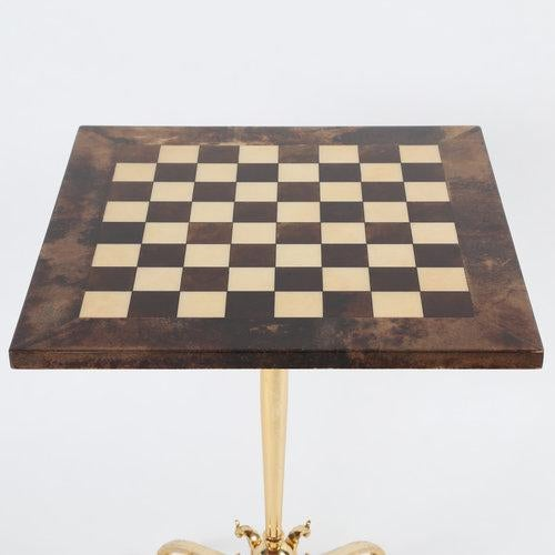 Square games table with a checkerboard top in tan and dark-brown lacquered goatskin, raised on a single polished-brass...