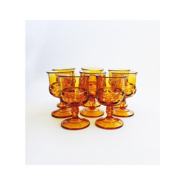 A set of 8 beautiful vintage goblets in amber colored glass. Lovely designs have been formed into the pressed glass....