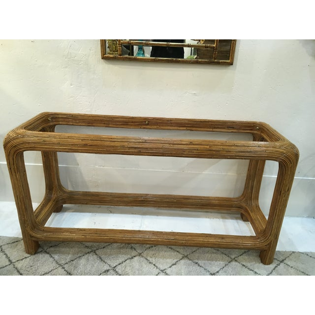 Waterfall style, split reed rattan console with glass top, in the style of Gabriella Crespi. The glass top on the table is...